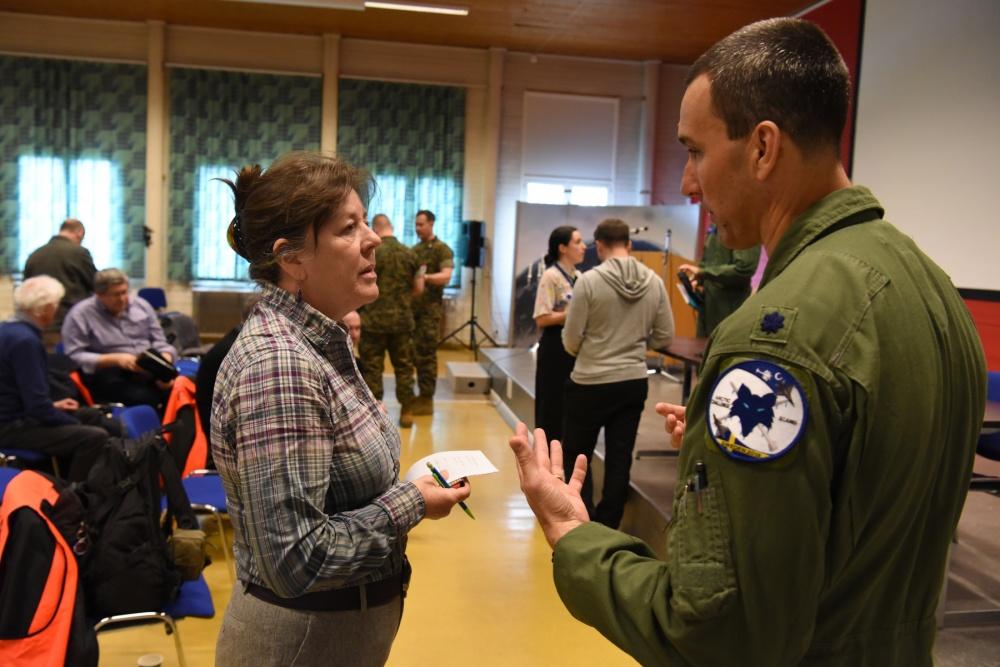 Christina Mackenzie speaking to a serviceman.